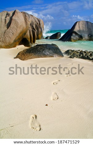 Granite stones on the beach with footprint in sand, La Digue, Seychelles - stock photo