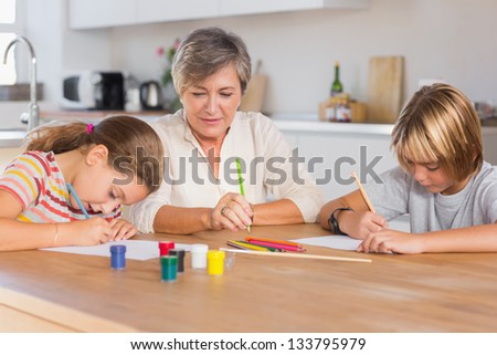Granny and her grandchildren drawing seriously in kitchen - stock photo