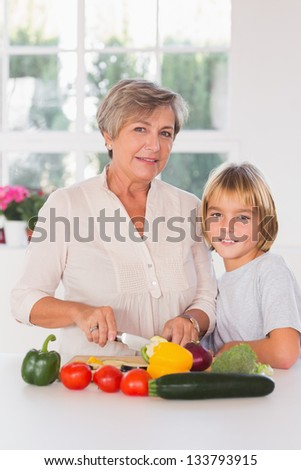 Granny cutting vegetables with her grandson in kitchen - stock photo