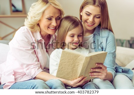 Granny, her daughter and granddaughter are reading a book and smiling while sitting on sofa at home - stock photo