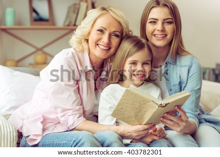 Granny, her daughter and granddaughter are reading a book, looking at camera and smiling while sitting on sofa at home - stock photo