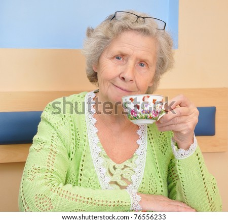 granny with cup of tea at home - stock photo