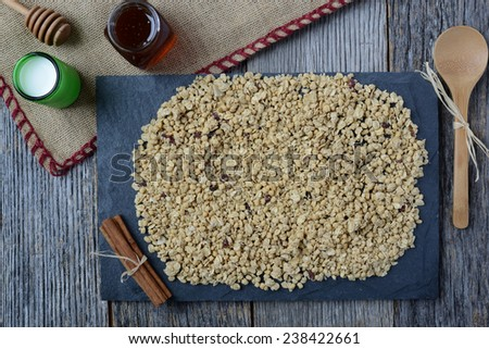 Granola and Honey with Cinnamon and Milk Covering  Gray Slate on Dark Wood Background with Burlap - stock photo