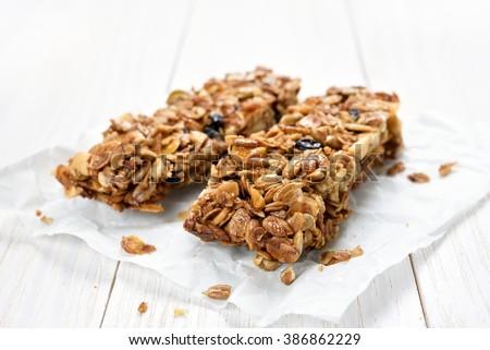 Granola bars on baking paper over white wooden background - stock photo