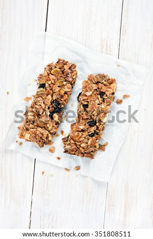Granola bars on baking paper over white wooden background, top view - stock photo