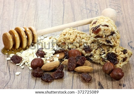 granola bars with ingredients on wooden background - stock photo