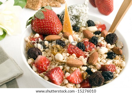Granola bowl: oats, rice, honey, peanuts, almonds, wax berry, white and red raisins, strawberries, glazed orange peel and fig  . Focus on the center of the bowl. - stock photo