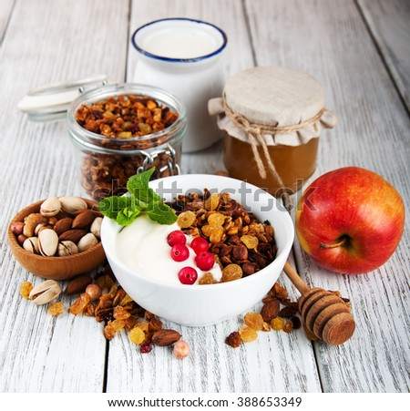 granola cereal with nuts and yogurt on a old wooden table