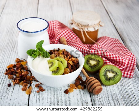 Granola cereal with nuts and yogurt on a old wooden table - stock photo