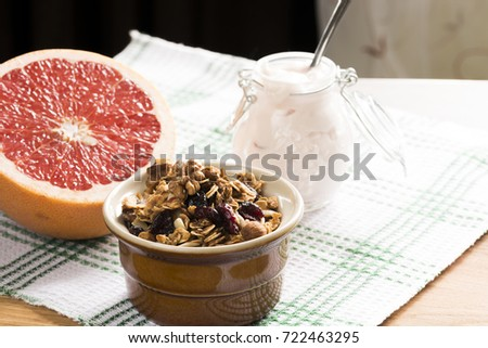 Granola from several types of cereals with nuts, coconut shavings and dried cranberries. Jar with homemade yogurt and grapefruit