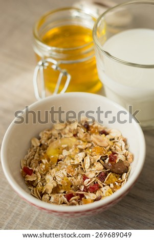 Granola in bowl with honey and milk, selective focus - stock photo