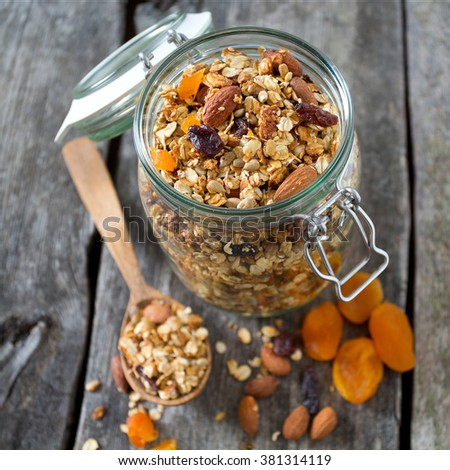 granola in glass jar on wooden table - stock photo