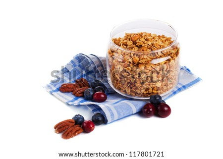 Granola in glass jar with nuts and berries isolated - stock photo