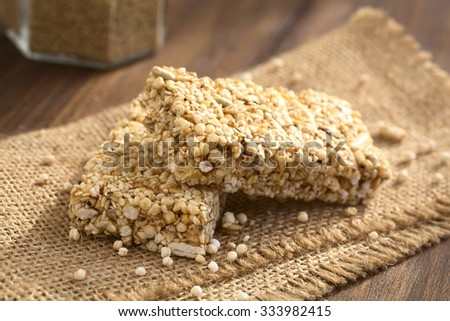 Granola or cereal bars made of popped quinoa, sesame seed, popped rice, sunflower seed, chia and honey, photographed with natural light (Selective Focus, Focus on the front edge of the upper bar) - stock photo
