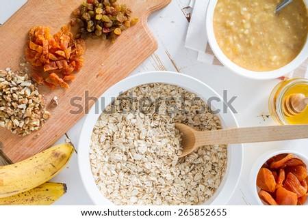 Granola preparation - ingredients, white wood background, top view - stock photo