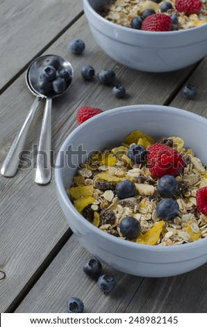 Granola with fresh berries on wooden background, healthy breakfast - stock photo