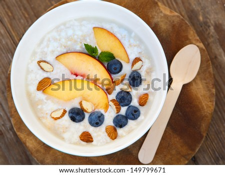 Granola with fresh organic blueberries, nectarines and almonds. Healthy breakfast - stock photo