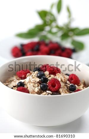 Granola with fresh organic raspberries and blueberries. Shallow DOF - stock photo