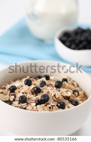 Granola with fresh wild blueberries and milk. Shallow DOF - stock photo