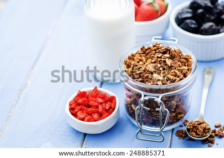 granola with milk, nuts, goji berries and strawberries. tinting. selective focus - stock photo