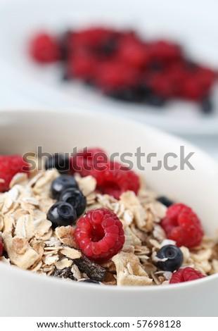 Granola with raspberries and blueberries. Shallow DOF - stock photo