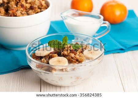 Granola with yogurt and banana in a bowl on white wooden background
