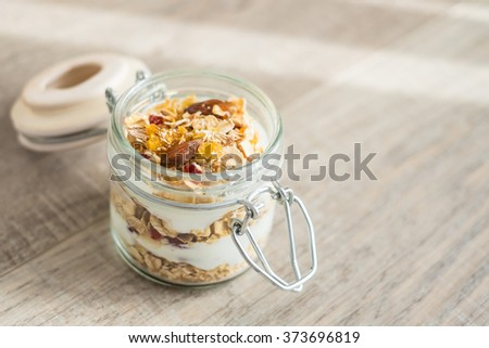 Granola with yogurt in a jar, selective focus - stock photo