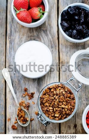 granola with yogurt, nuts, goji berries and strawberries. tinting. selective focus - stock photo