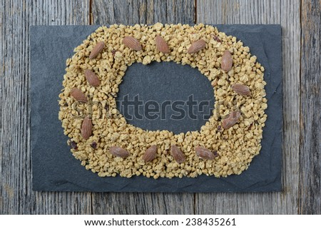 Granola Wreath with  Almonds on Slate and Dark Wood Background - stock photo
