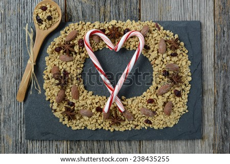 Granola Wreath with Wood Spoon and Candy Canes in the Shape of a Heart on Slate and Dark Wooden Background - stock photo