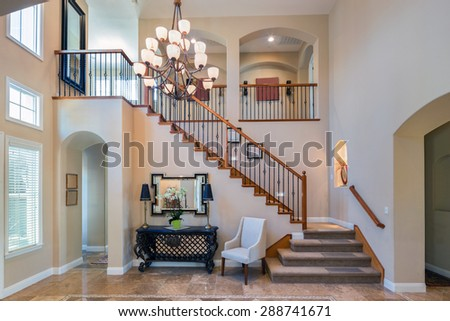 Grant Interior with staircase in large private home with granite floor and large chandelier. - stock photo