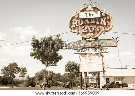 GRANTS, USA - SEPTEMBER 20; Motor cyclists cross road under historic sign aged photo effect on Historic Route 66 on September 20, 2015, Grants NM USA vintage Roaring 20's liquor store sign