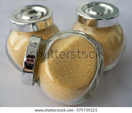 Granulated garlic in transparent jars on a white background - stock photo