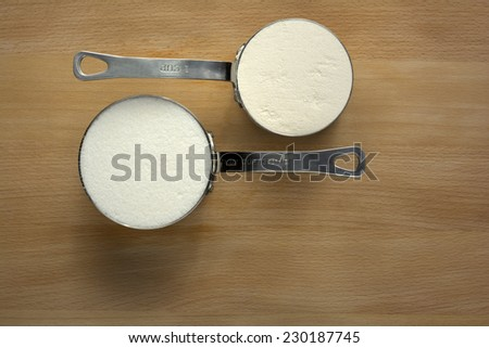Granulated Sugar and Flour in Metal Measuring Cup on Wood Background - stock photo