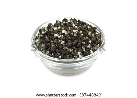 granule fertilizer and humus in glassware on a white background