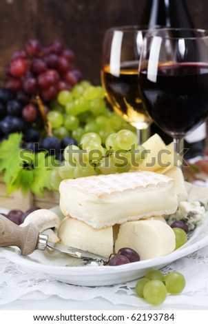 Grape and cheese with a bottle and glasses of red and white wine - stock photo