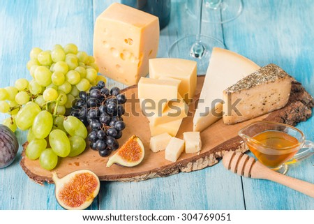 Grape, assorted cheese, figs and honey with red wine on blue wooden background. - stock photo