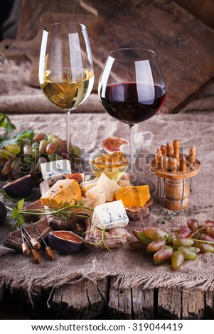 Grape, cheese, figs and honey with a glasses of red and white wine.Cheese Board.selective focus - stock photo