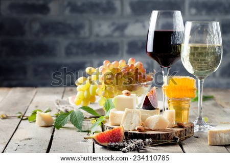 Grape, cheese, figs and honey with a glasses of red and white wine on a stone and wood background.