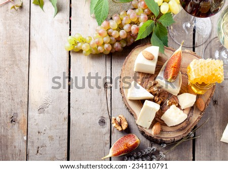 Grape, cheese, figs and honey with a glasses of red and white wine on a stone and wood background. - stock photo