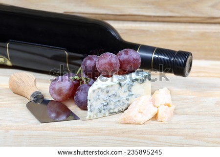 Grape, delicious cheese and bottle of wine on natural wooden background - stock photo
