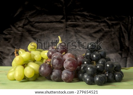 Grape fruit on green table with black background - stock photo