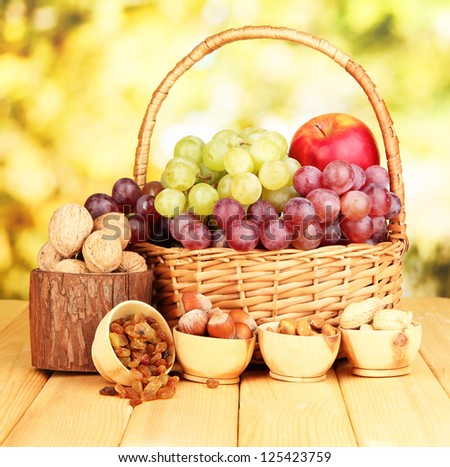 Grape in basket with nuts on wooden table - stock photo