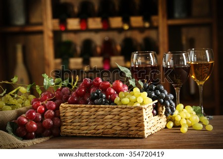 Grape in wicker box on a table on wine bottles background - stock photo