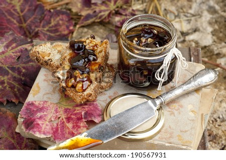 grape jam in glass jar with cantuccini on an old vintage book - stock photo