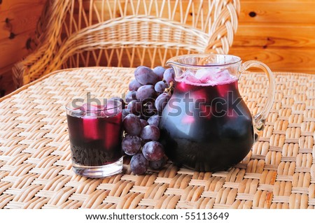 Grape juice in a glass end jug on the table - stock photo