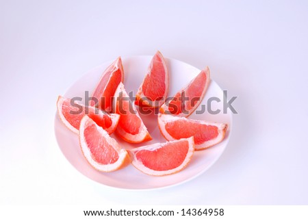 Grapefruit arranged on a plate against graduated white background - stock photo