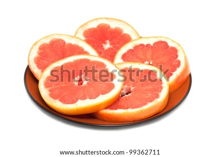 Grapefruit circles are laid out on a brown plate - stock photo