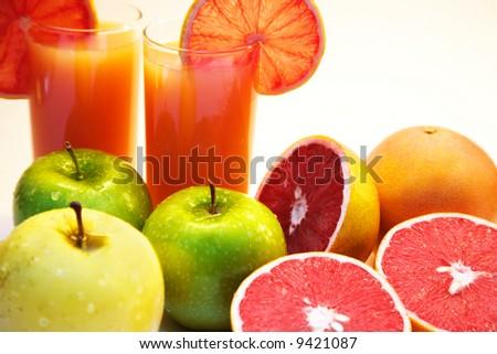 Grapefruit juice and fruits isolated on white - stock photo