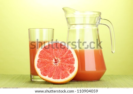 Grapefruit juice and grapefruit on bamboo mat on green background